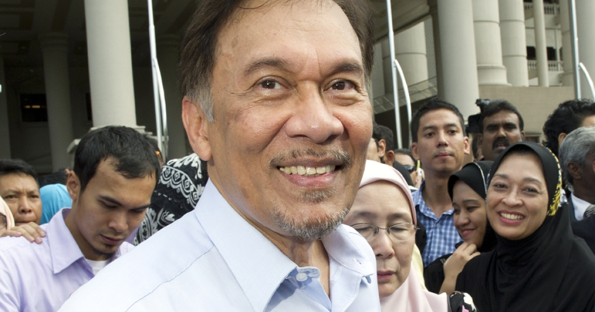 Malaysian opposition leader Anwar Ibrahim smiles as he wals to his supporters celebrating the verdict of his trial outside the court in Kuala Lumpur on January 9, 2012.</p>