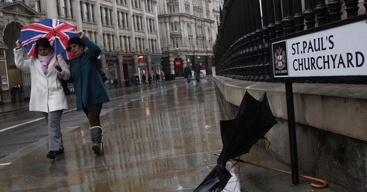 Two women walk in the pouring rain outside St. Paul's Cathedral in London, United Kingdom, on Jan. 3, 2012.</p>