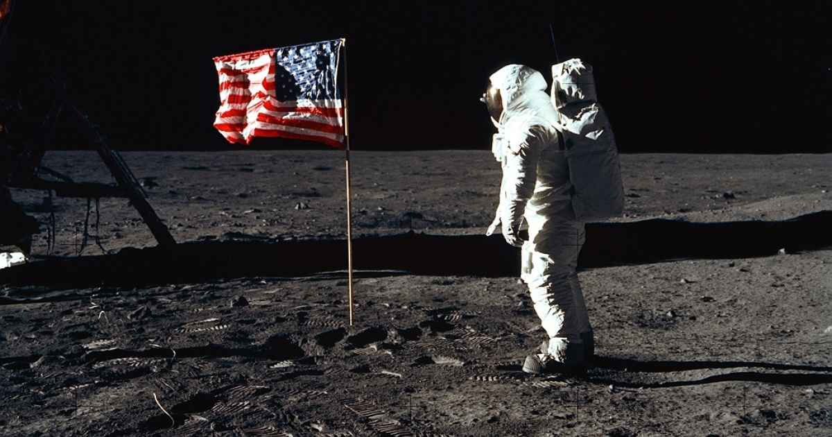 Astronaut Edwin E. Aldrin, Jr., the lunar module pilot of the first lunar landing mission, stands next to a United States flag July 20, 1969 during an Apollo 11 Extravehicular Activity (EVA) on the surface of the Moon.</p>