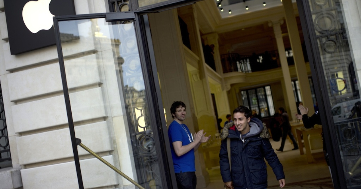 A customer leaves an Apple store in Paris on September 21, 2012.</p>