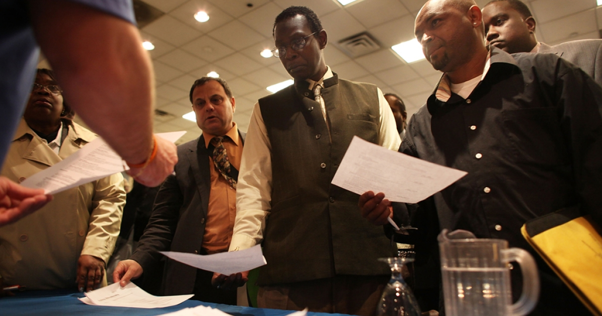 Job seekers line-up to give their resumes to a representative of an employment agency at a job fair at a Holiday Inn on April 18, 2012.</p>