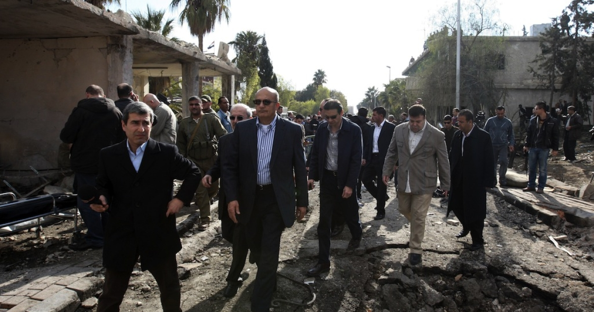 Deputy Arab League Seretary General Samir Seif al-Yazal inspects with a group of Arab observers the site of a suicide attack, which targeted the Syrian General Intelligence headquarters, in Damascus on December 23, 2011.</p>