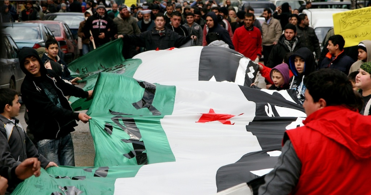 Demonstrators hold the former Syrian flag during a protest against the Syrian regime and its deadly crackdown on dissent in the northern Lebanese city of Tripoli on January 27, 2012. Western and Arab nations could make public their draft resolution condemning Syria's deadly crackdown on protesters when the UN Security Council convenes to discuss the escalating crisis.</p>