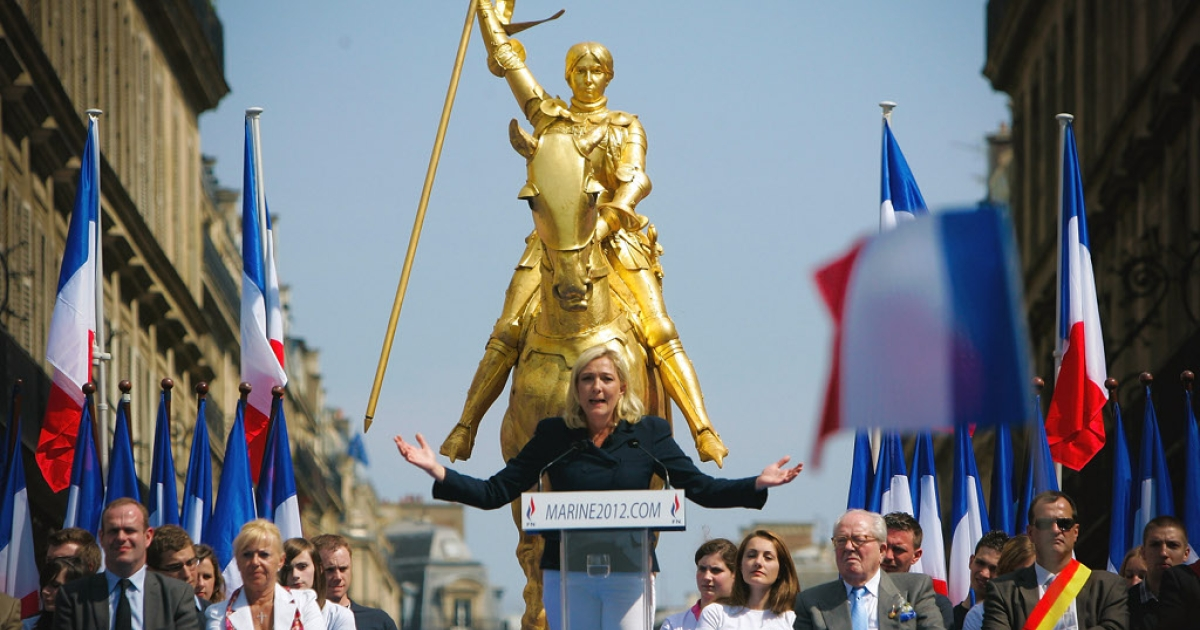 Joan of Arc looks down on far-right National Front leader Marine le Pen at a rally last spring in Paris.  France's presidential candidates are scrambling to claim St. Joan's blessing for their campaigns on her 600th birthday.</p>