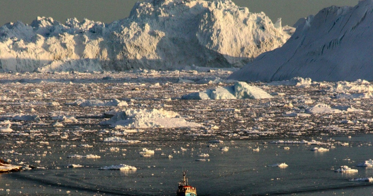 A boat skims through the melting ice in the Ilulissat fjord on Aug. 28, 2008, on the western coast of Greenland. This picture shows the Arctic ice is melting at an alarming rate.</p>