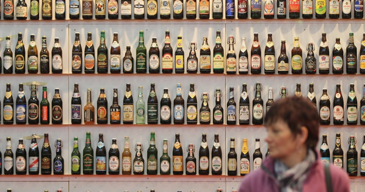 A woman walks among hundreds of bottles of German beer, on Jan. 21, 2011.</p>
