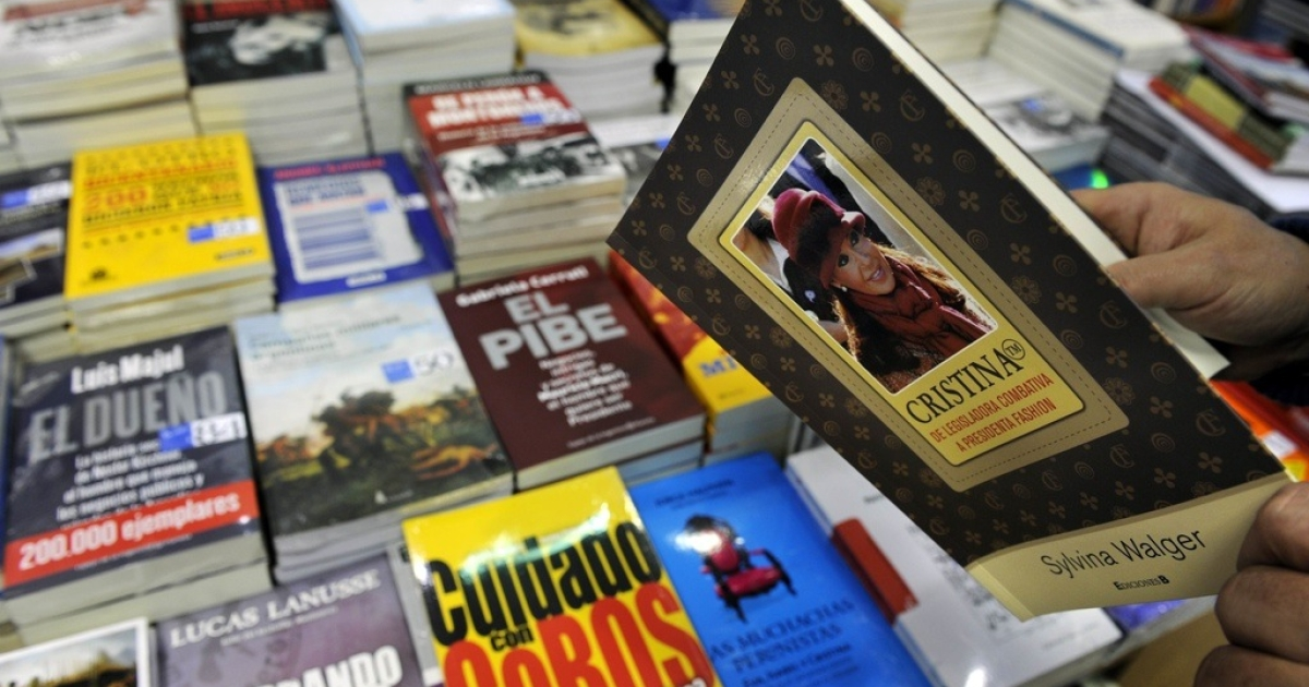 A man reads a biography of Argentine President Cristina Fernandez de Kirchner next to a table with politicians' biographies on Sept. 1, 2010.</p>