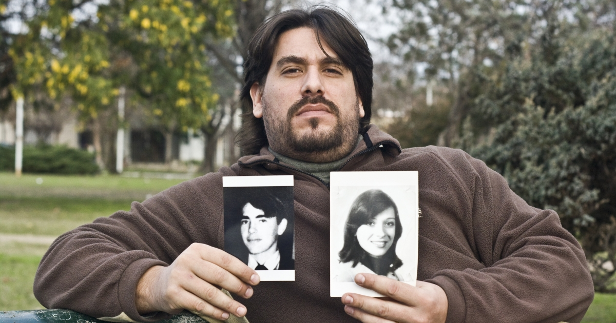 Guillermo Perez Roisinblit holds pictures of his biological parents. He's one of hundreds of victims of the Argentine military regime's baby abduction scheme.</p>