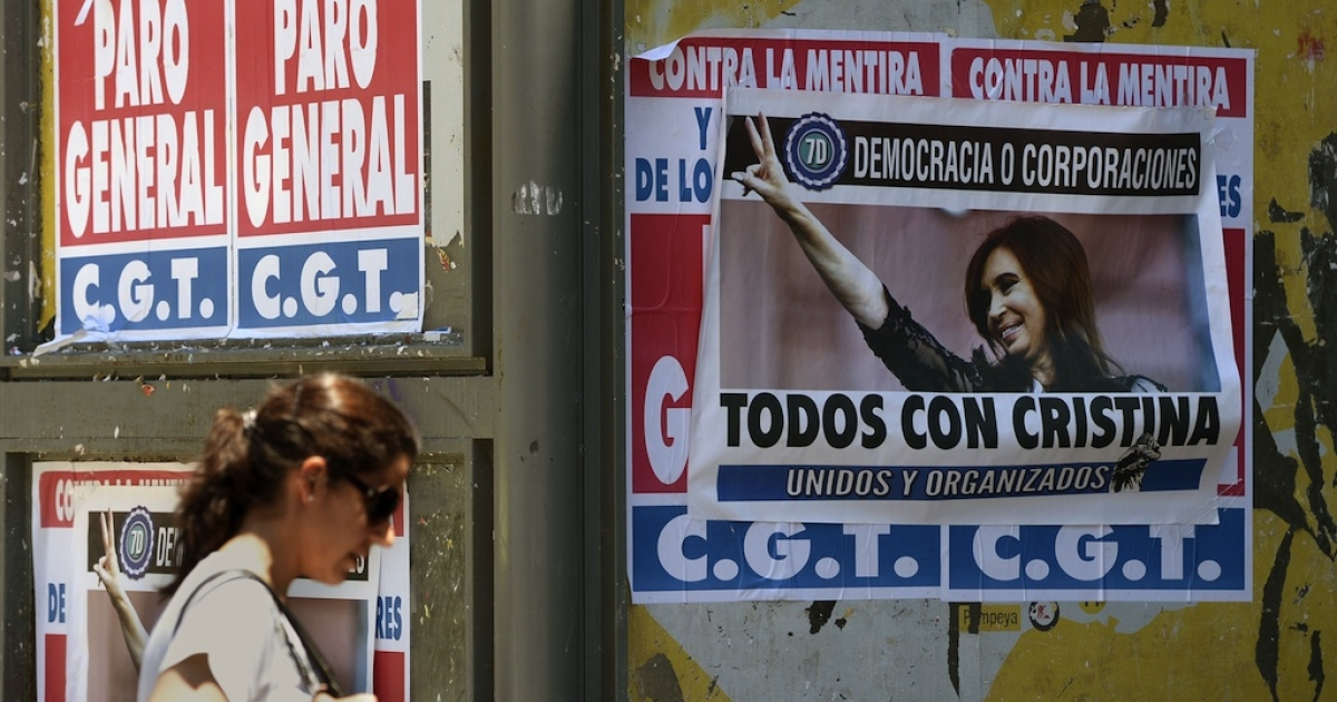 A woman walks next to banners supporting and against a unions' strike that blocks the approaches to the capital, on November 20, 2012 in Buenos Aires. A general strike was called Tuesday by the working unions opposing the government of President Cristina Fernandez de Kirchner to protest against the taxes on wages.</p>