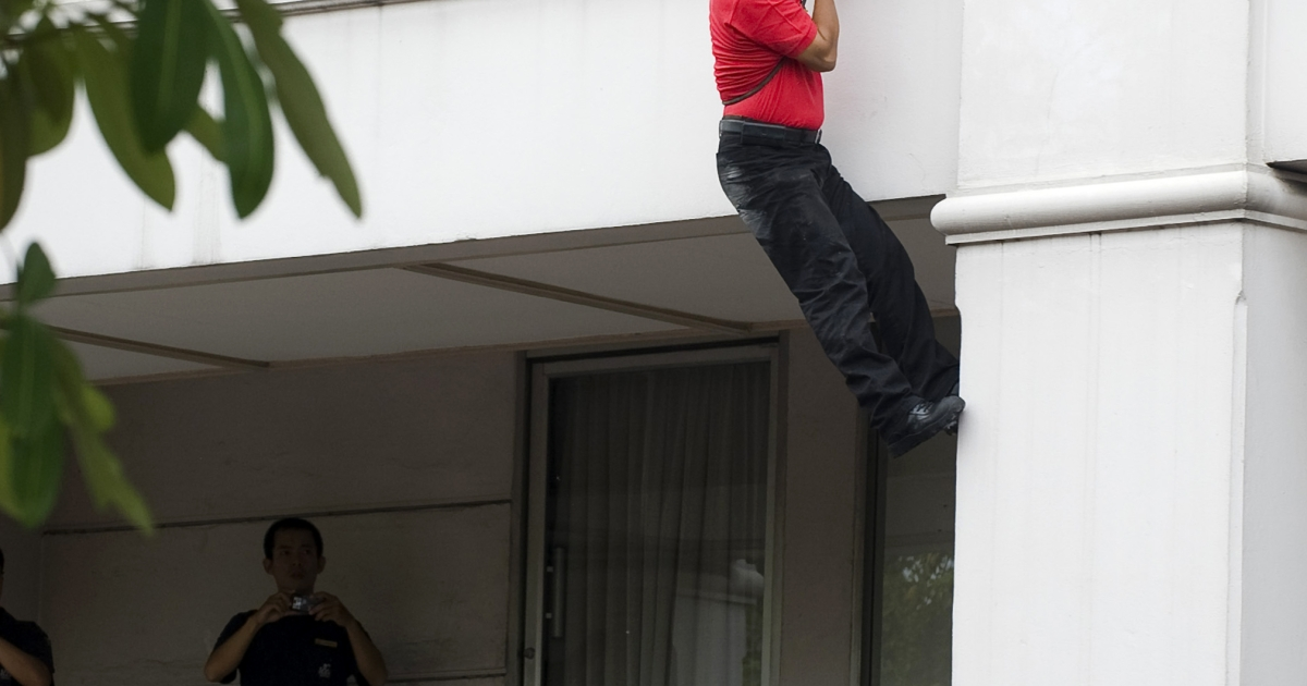 'Red Shirt' anti-government leader Arisman Pongruanrong flees police on April 16, 2010, at a downtown hotel in Bangkok using a rope.</p>