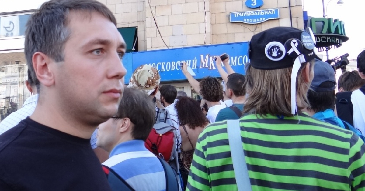 Yevgeny Arkhipov at an opposition protest. He believes the movement's while ribbon symbol will soon be left in