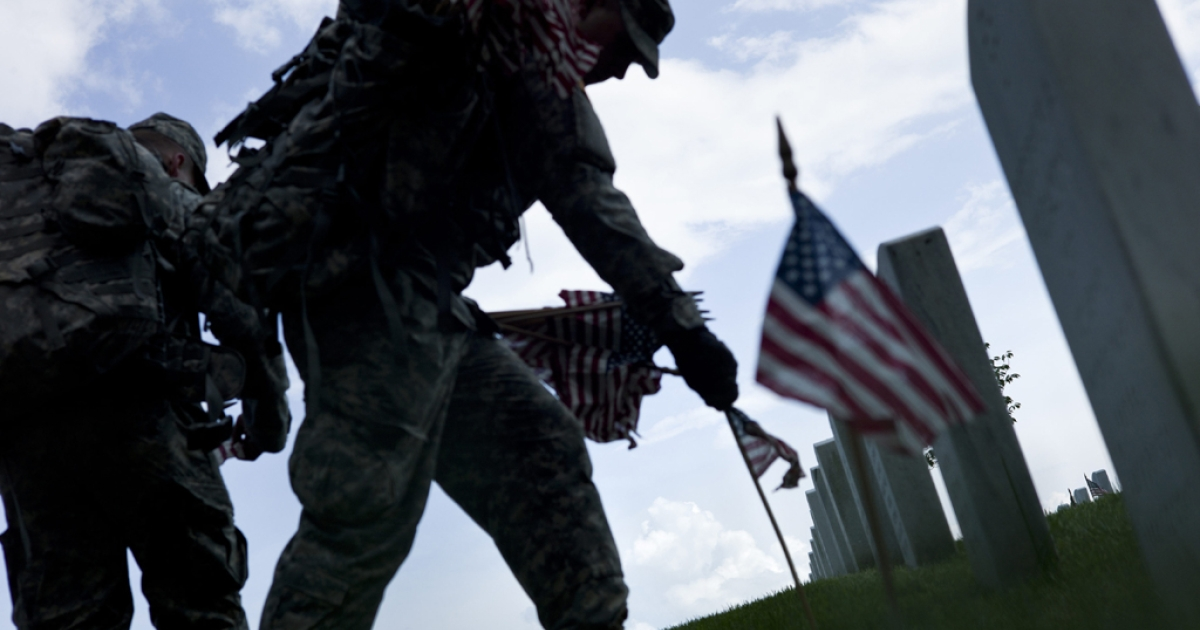 A soldier plants a flag at a grave in Arlington National Cemetery May 24, 2012 in Washington, D.C. Flags were placed at more than 220,000 headstones this year in the ceremony, which has taken place every year since 1948.</p>