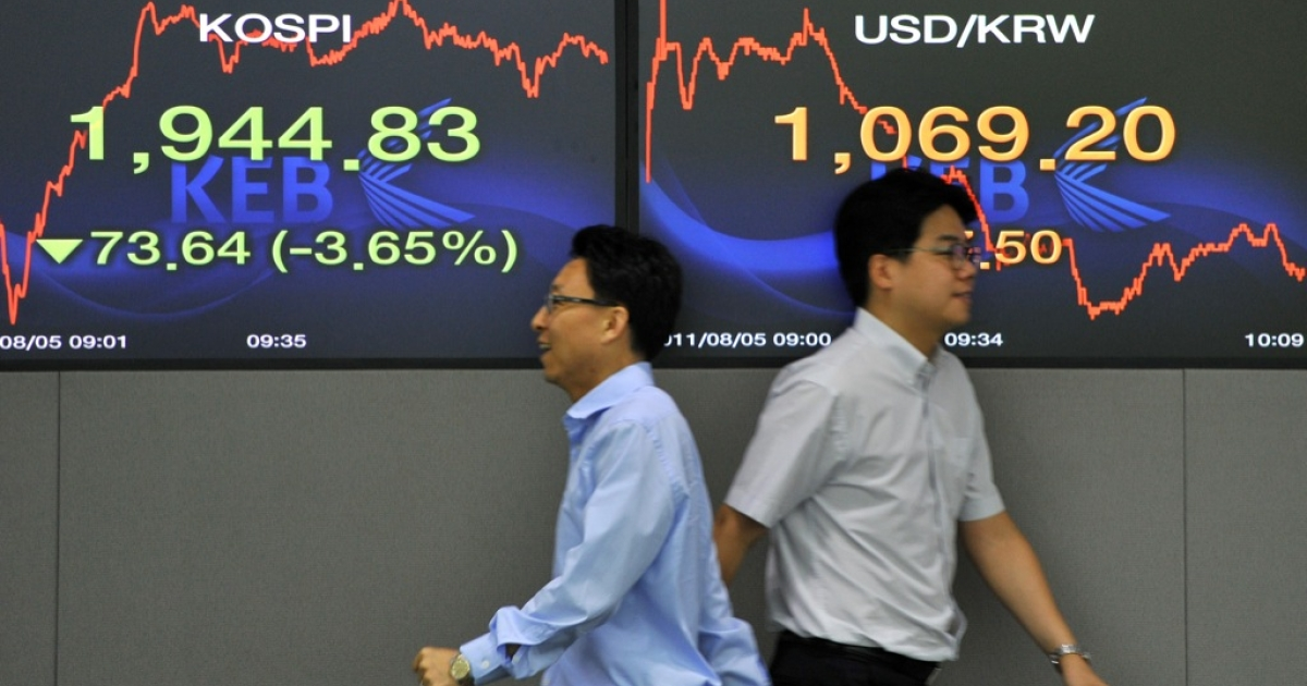 Currency dealers walk past screens showing South Korea's benchmark stock index (L) and the Korean won/USD exchange rate (R) in a dealing room at the Korea Exchange Bank in Seoul on August 5, 2011.</p>