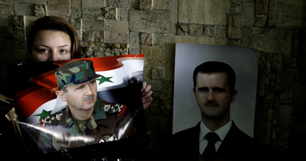 A Syrian woman holds up a picture of Syrian President Bashar al-Assad as she follows his speech on television at a cafe in Damascus today.</p>