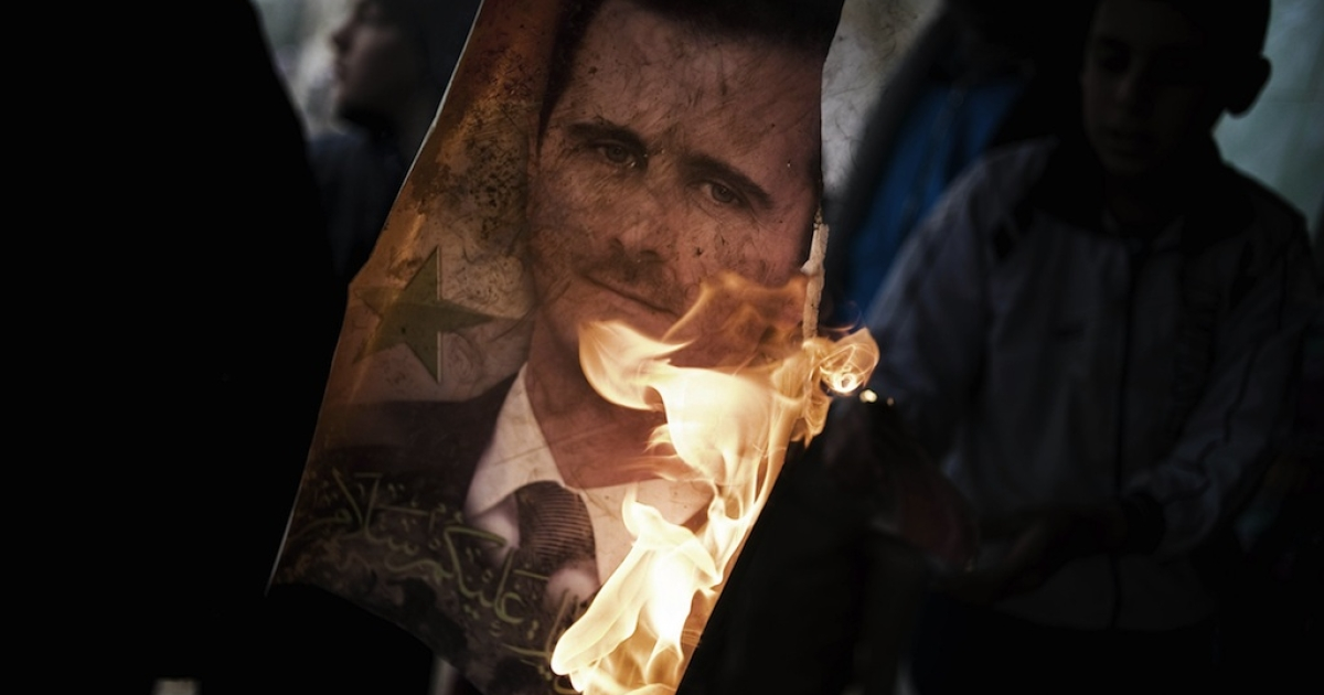 A member of the Free Syrian Army holds a burning portrait of embattled President Bashar al-Assad in Al-Qsair, on January 25, 2012.</p>