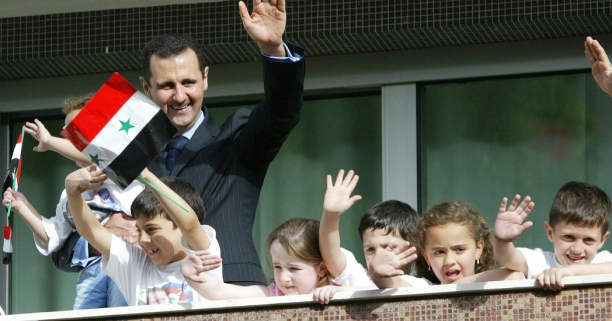 Children join Syrian President Bashar al-Assad as he waves to his supporters in Damascus.</p>