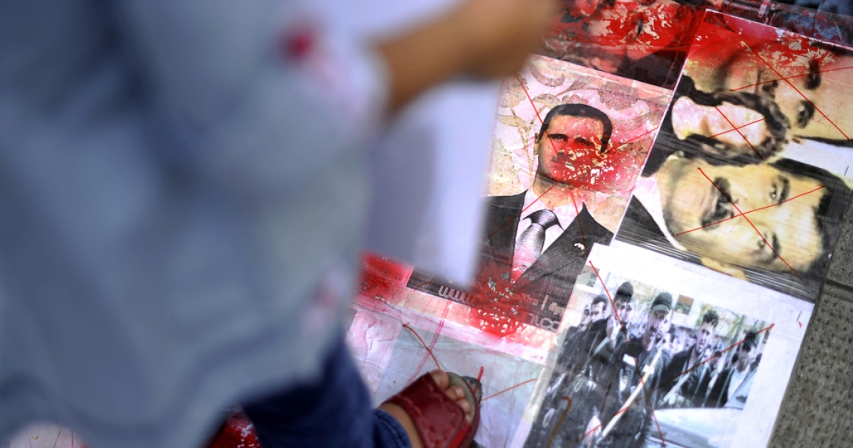 A child, holding a placard, stands on pictures of members of the syrian government including President Bashar al-Assad (C) during a protest gathering activists, including Syrians living in Switzerland opposed to the syrian regime in front of the consulate on August 12, 2011 in Geneva. Syrian forces launched assaults on flashpoint areas, killing at least two people as they pursued a crackdown on dissent ahead of expected mass protests after Ramadan Friday prayers.   AFP PHOTO / FABRICE COFFRINI (Photo credit should read FABRICE COFFRINI/AFP/Getty Images)</p>