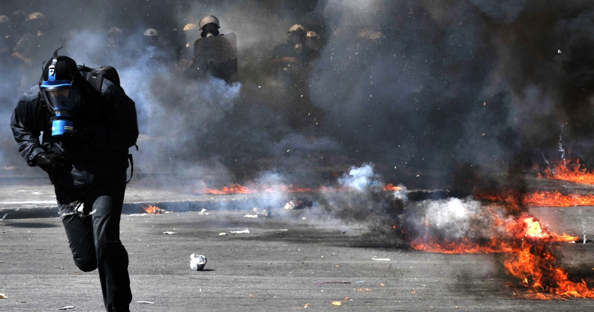 A protester runs from police in Athens on Wednesday.</p>