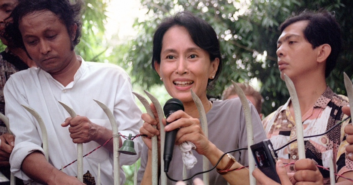Pro-democracy leader and Nobel Peace laureate Aung San Suu Kyi addresses hundreds of anxious Burmese supporters from the main gate of her family compound in Rangoon on July 14, 1995.</p>