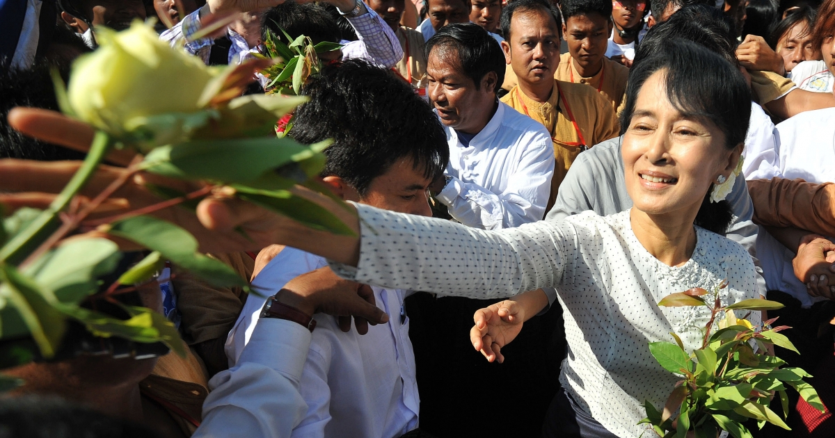 Burmese opposition leader Aung San Suu Kyi is surrounded by supporters as she leaves the Thanlyin township election commission office after she registered to run as a candidate in upcoming by-elections, on the outskirts of Yangon on January 18, 2012.</p>