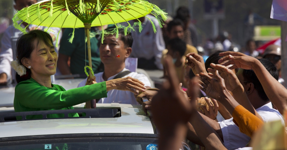 PATHEIN, MYANMAR - FEBRUARY 7: Myanmar opposition leader Aung San Suu Kyi greets the crowds from the top of a vehicle during campaigning in the Delta region on her second campaign trip on February 7, 2012 in Pathein, Myanmar.  Aung San Suu Kyi is beginning her election campaign as an official candidate ahead of the April 1 by-elections. This was the first time in twenty years that Suu Kyi has visited the Delta region. (Photo by Paula Bronstein/Getty Images)</p>