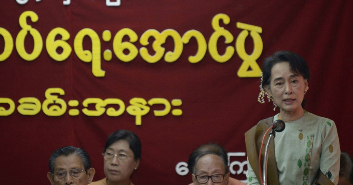 Myanmar opposition leader Aung San Suu Kyi (R, standing) delivers a speech to mark the 65th anniversary of Myanmar's independence at the head office of the National League for Democracy (NLD) party in Yangon on January 4, 2013. Suu Kyi has been criticized for taking money from some of Myanmar's most notorious cronies.</p>