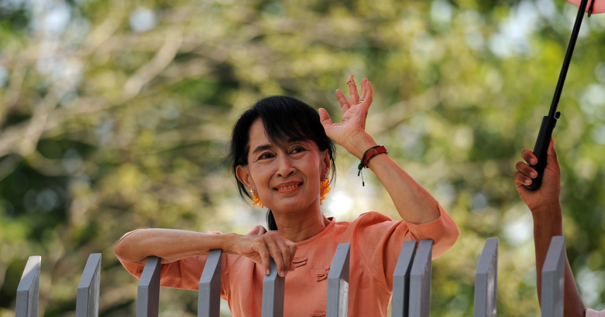 Myanmar opposition leader Aung San Suu Kyi greets supporters from the gate of her house on the occasion of festivities marking the country's new year in Yangon on April 16, 2012. Suu Kyi plans to leave Myanmar for the first time in 24 years, to visit Britain and Norway.</p>