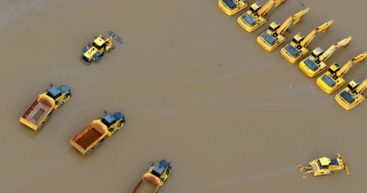 This aerial photograph shows giant mining trucks and excavators submerged as flood waters devastate much of Brisbane on Jan. 13, 2011.</p>
