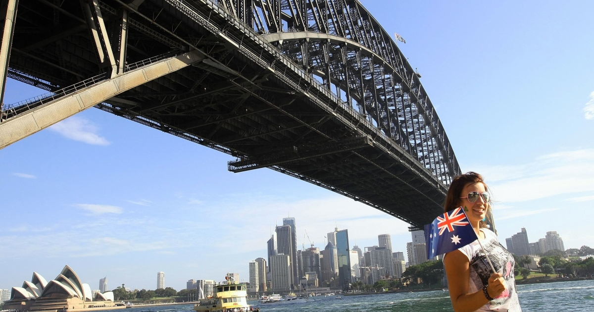A teenager poses near the Sydney Harbour Bridge and Sydney Opera House on Australia Day, January 26, 2011. Quite a contrast to the Sydney seen by many teenagers brought to Australia on prospective spouse visas.</p>