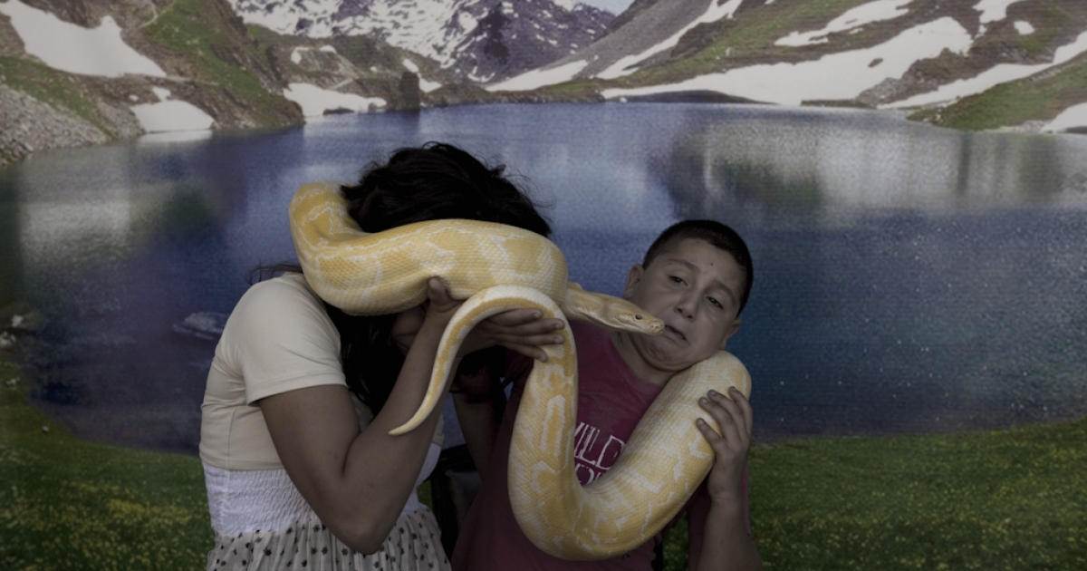 Arab Israeli children pose with a pet snake at an amusement park in the northern Israeli city of Acre on August 31, 2011, as Muslims celebrated the Eid al-Fitr holiday which marks the end of the holy fasting month of Ramadan.</p>