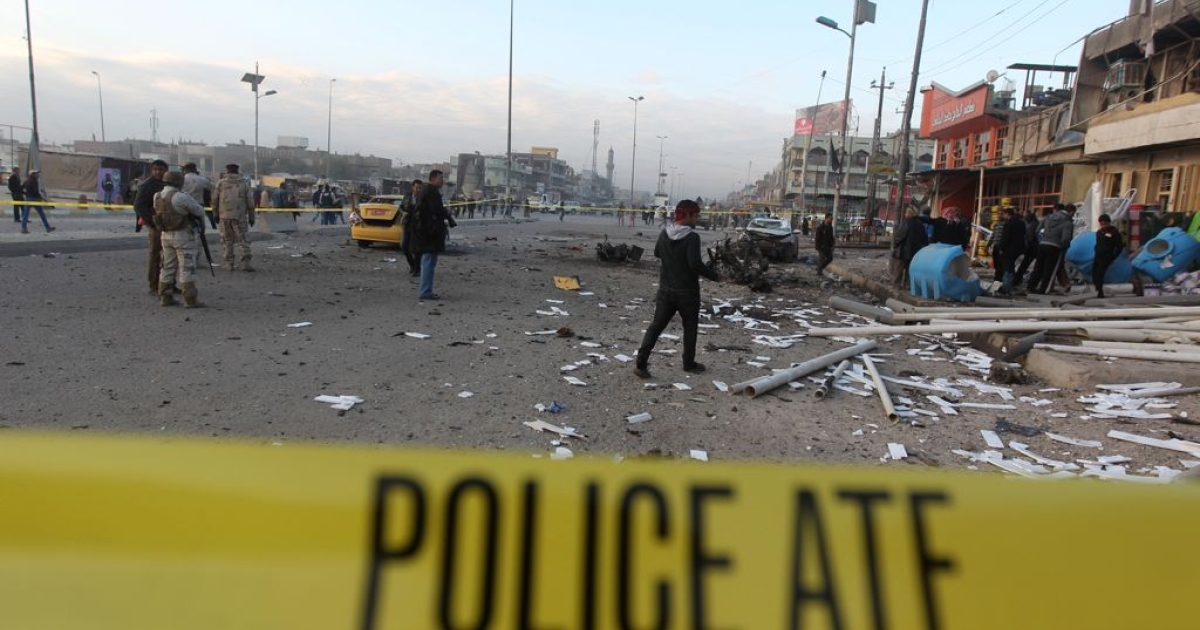 Iraqi security forces inspect the site of a blast after a bomb ripped through a group of workers in Sadr City in Baghdad on Jan. 24, 2012.</p>