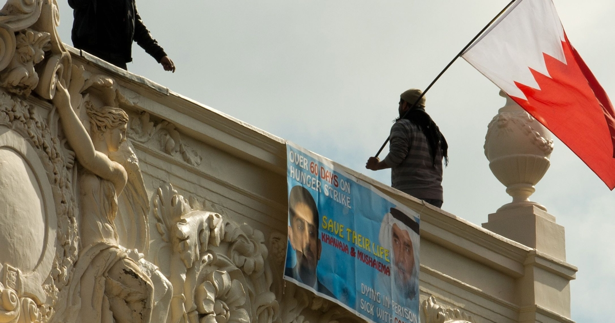 A protester waves a Bahraini national flag from the top of the Bahraini Embassy in central London on April 16, 2012 during a protest over the imprisonment of political activist Abdulhadi al-Khawaja.</p>