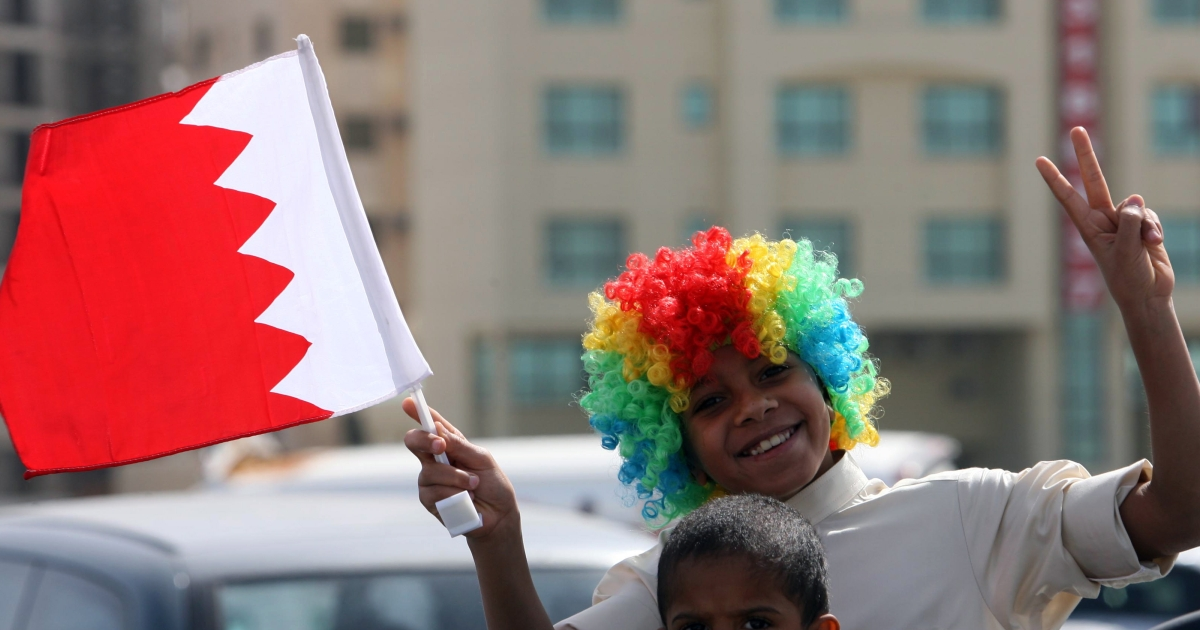 A young Bahraini pro-government supporter waves his national flag during a gathering near the Al-Fateh mosque following Friday's noon prayers in the capital Manama on February 18, 2011 as angry Shiites burried the dead of a violent police raid on anti-regime protesters.</p>