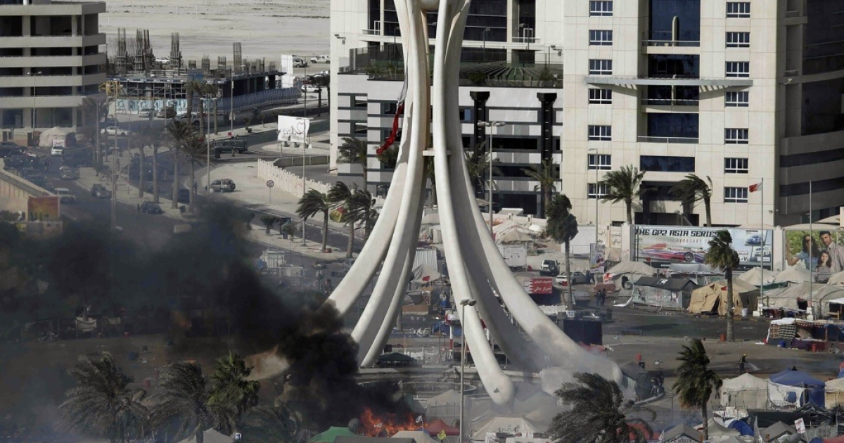 Black smoke rises from burning tents as Bahraini security troops raid the one-month-old pro-democracy sit-in at Pearl Square in the capital Manama on March 16, 2011.</p>
