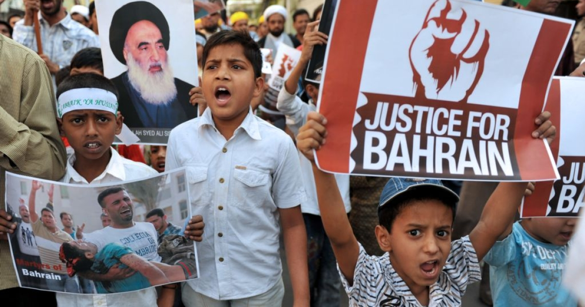 Young Indian Muslims pose with placards during a protest rally against the ongoing political turmoil in Bahrain on March 27, 2011.</p>