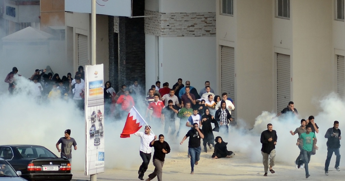 Bahraini anti-government protesters run for cover from tear gas during clashes with riot police near the headquarters of the main Shiite opposition group, Al-Wefaq, in Zinj Village, west of Manama, on December 23, 2011.</p>