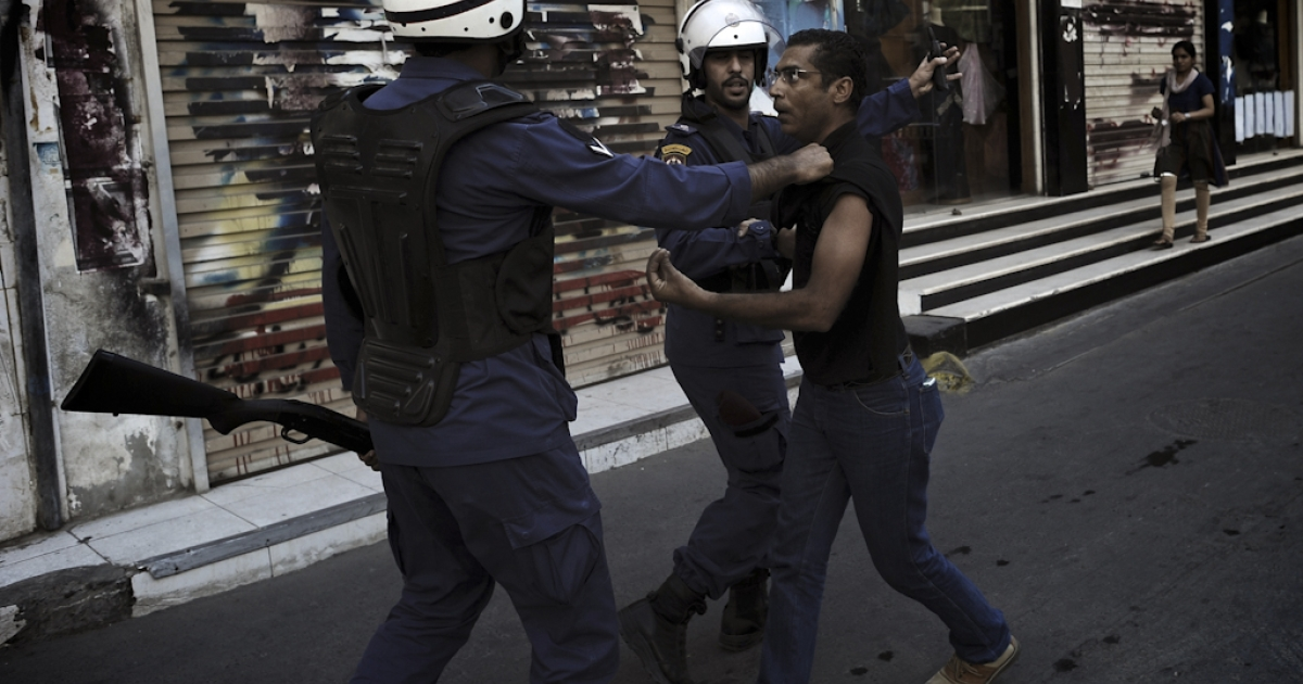 A Bahraini Shiite protester is detained by riot police during an anti-government demonstration in the centre of the capital Manama on September 21, 2012.</p>