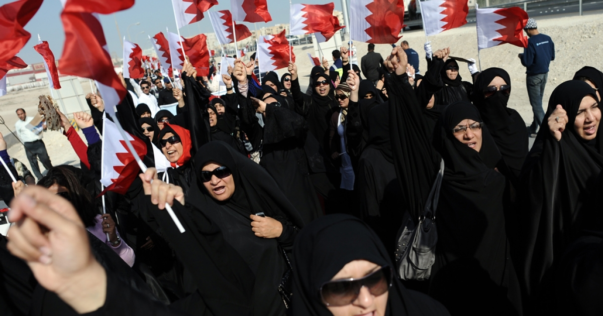 Bahraini women wave their national flag during a rally of Shiite employees who were dismissed from their jobs over pro-democracy protests, near the ministry of labour in Isa Town, south of the capital Manama, on December 27, 2011. Demonstrations have been rekindled in the days leading up to the first anniversary of Bahrain's Shiite uprising on February 14, 2011. AFP PHOTO/STR</p>