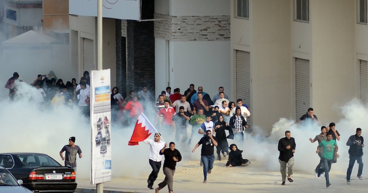 Bahraini anti-government protesters run for cover from tear gas during clashes with riot police near the headquarters of the main Shiite opposition group, Al-Wefaq, in Zinj Village, west of Manama, on December 23, 2011. AFP PHOTO/STR</p>