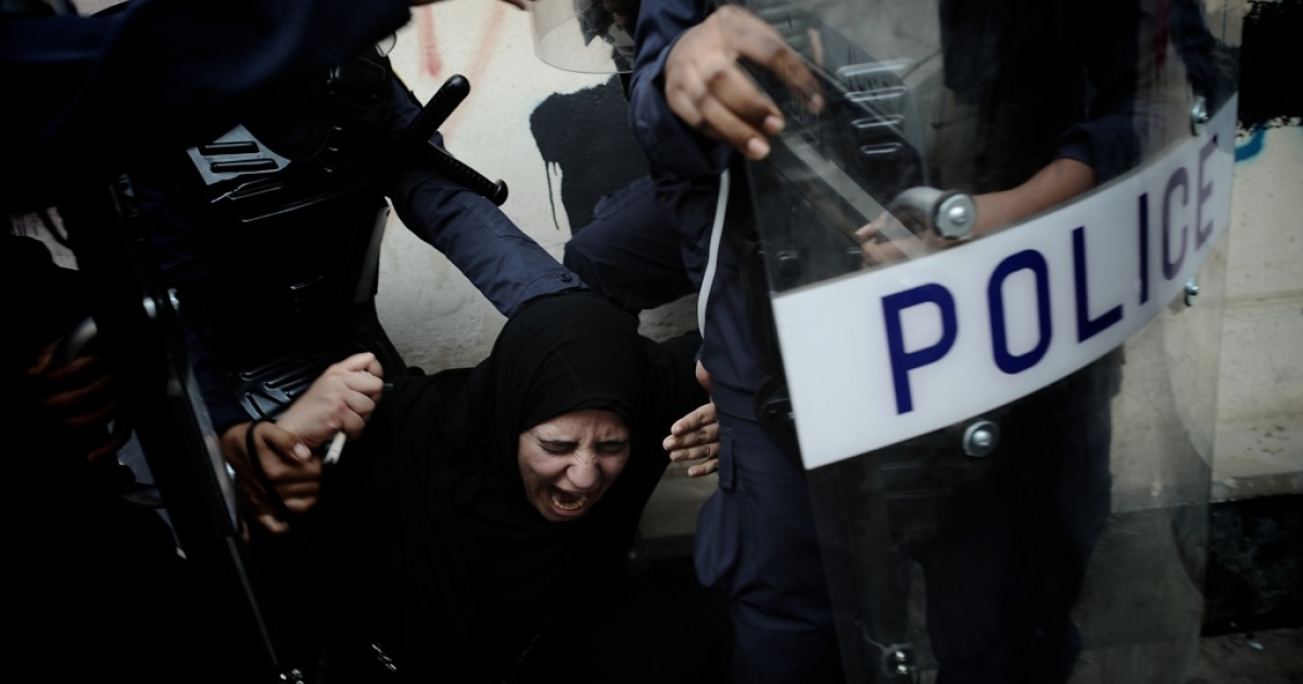 A Bahraini Shiite protester reacts as she is detained by riot police during an anti-government demonstration in the centre of the capital Manama on September 21, 2012.</p>