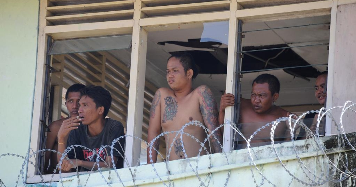 Prisoners occupying Kerobokan prison in Bali, Indonesia watch preparations for the evacuation of women and foreigners</p>