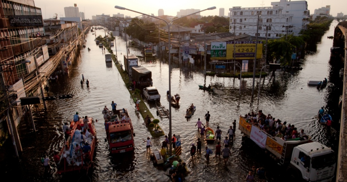 Thai residents make their way across a flooded street close to the rising waters of the Chao Phraya river on October 30, 2011 in Bangkok, Thailand.</p>