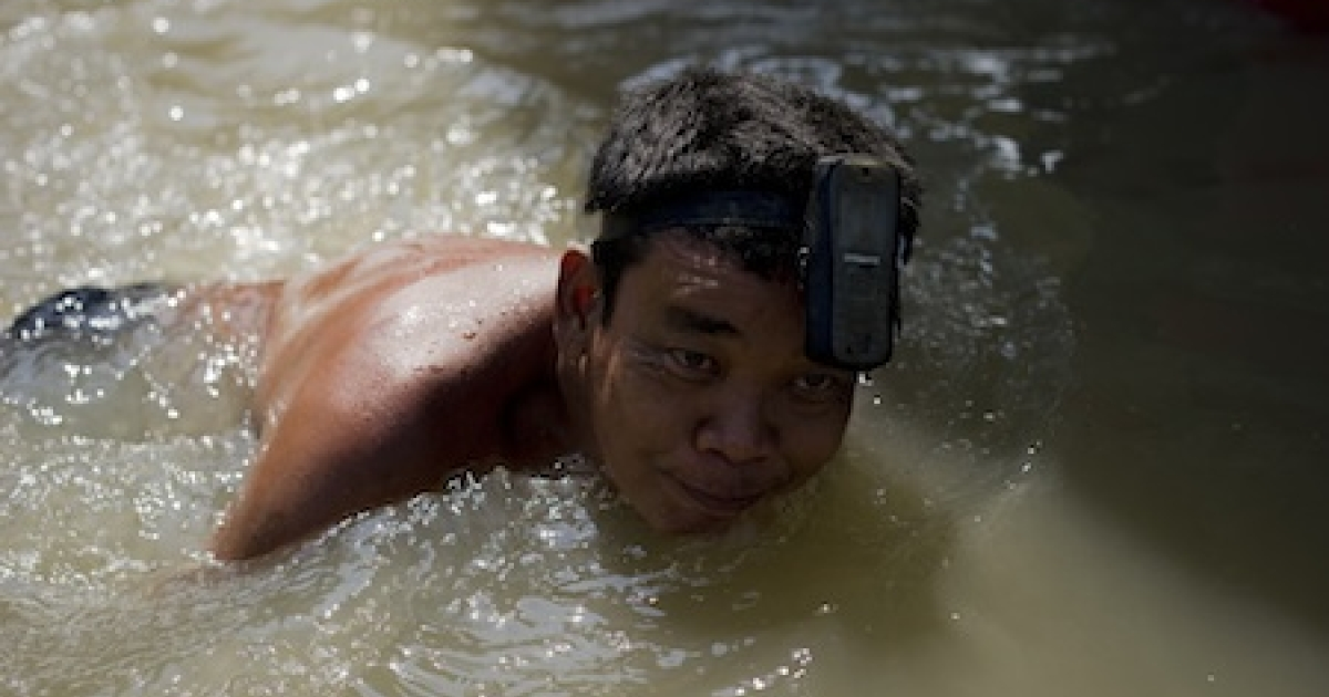 A local resident swims with a mobile phone attached to his head in floodwaters after a mud and sandbag wall collapsed in Bang Bua Thong in Nonthaburi province, suburban Bangkok, on October 19, 2011. Thailand's premier urged the kingdom's rival political factions on October 19 to work together to tackle the worst floods in decades.</p>