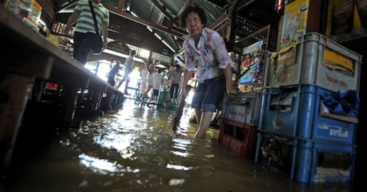 A Thai woman cleans the floor of a flooded market in Bangkok on October 28, 2010.</p>