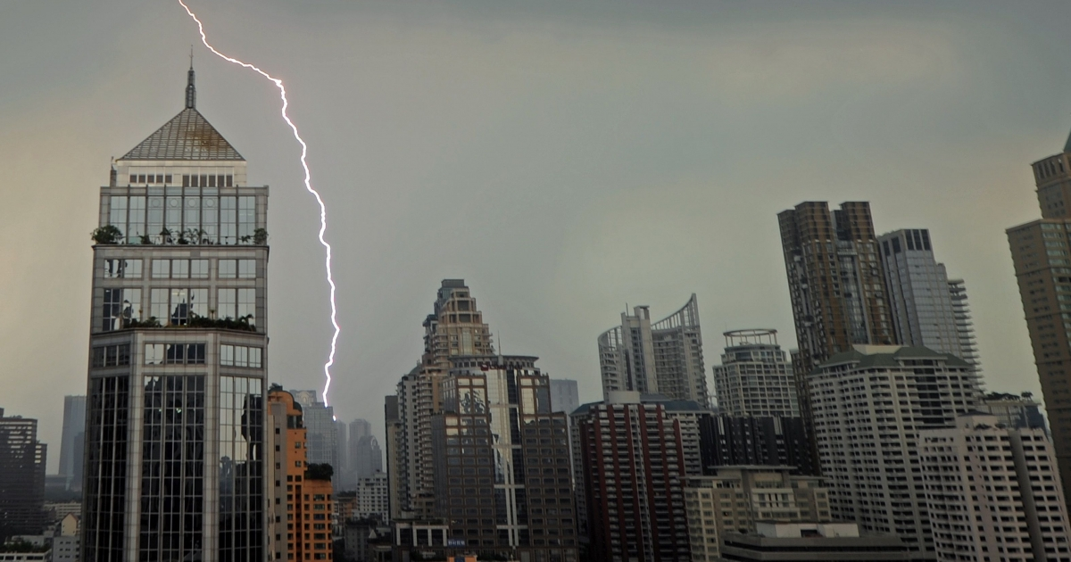 Lightening streaks across the skyline during heavy rain in Bangkok on March 26, 2012.</p>