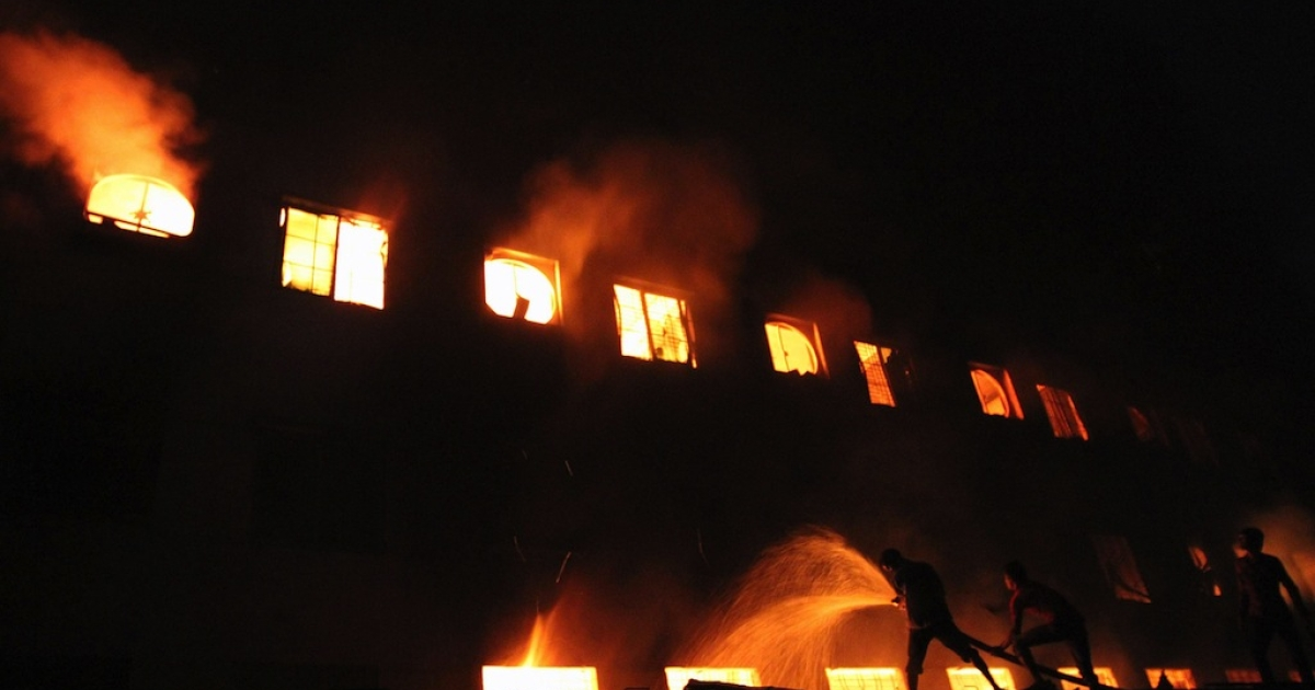 Citizens and firefighters fight to extinguish a fire in the Tazreen Fashion plant in Savar, Bangladesh on Nov. 25, 2012.</p>