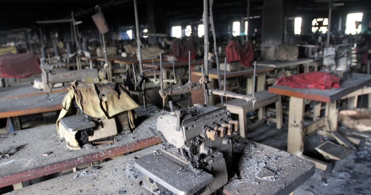 The skeletal remains of rows of sewing machine tables, covered in ash after a fire at the Tazreen Fashions factory outside Dhaka, Bangladesh.</p>