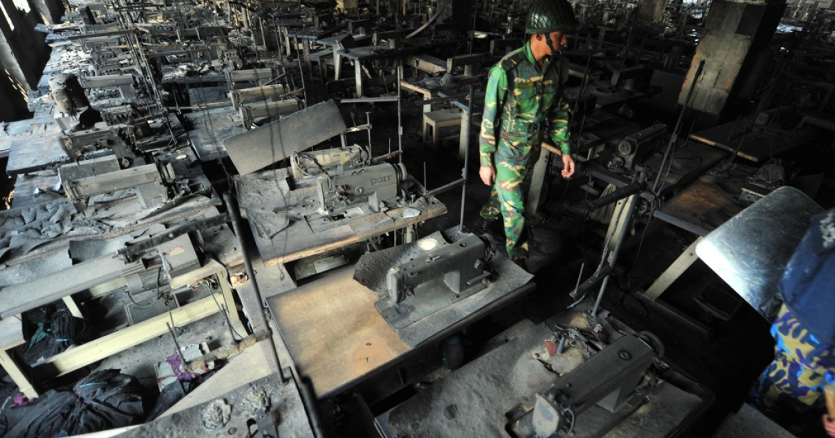 A Bangladeshi soldier walks through rows of burnt sewing machines after a fire in the nine-storey Tazreen Fashion plant near Dhaka on November 25, 2012.</p>