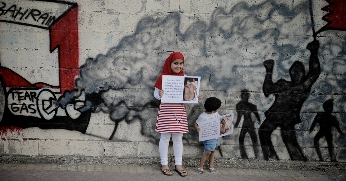 Bahraini children hold up pictures of tortured democracy activists as they pose in front of graffiti depicting a scene of anti-government demonstrations in the Shiite village of Barbar on the western outskirts of the capital Manama.</p>