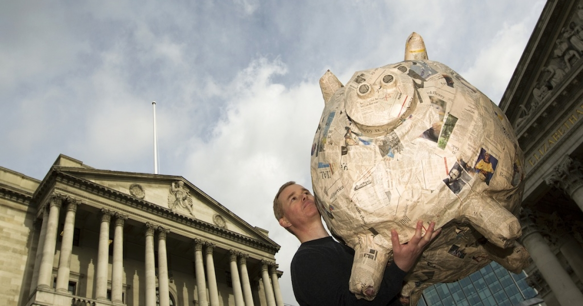Jason Riddle, co-founder of 'Save Our Savers' lifts a giant papier mache piggy bank outside the Bank of England in London on October 6, 2011. The Bank of England agreed to inject $116 billion into the British economy on Oct. 6, 2011.</p>